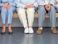 Several seniors sit in a waiting room, leg pain may be related to medication.