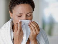 Mujer estornudando en una servilleta - Informacion que debe saber acerca de Tamiflu
