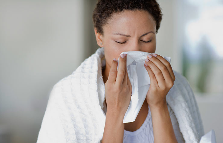 Woman sneezing into tissue, what you should know about Tamiflu