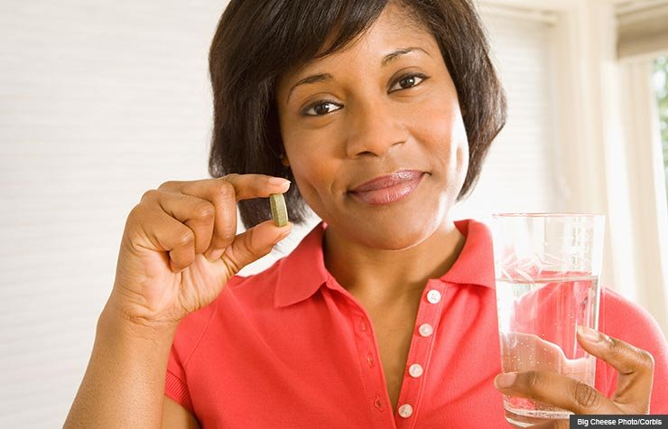 Woman holding Vitamin D pill, Blood pressure benefits
