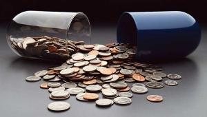Monedas en una cápsula rota - Los altos costos de los medicamentos contra el cáncer