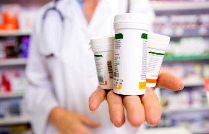 Empleado de farmacia con varios frascos de medicamentos en su mano