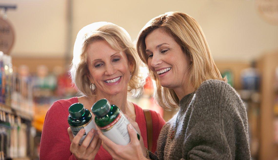 Dos mujeres observan unos recipientes con vitaminas.