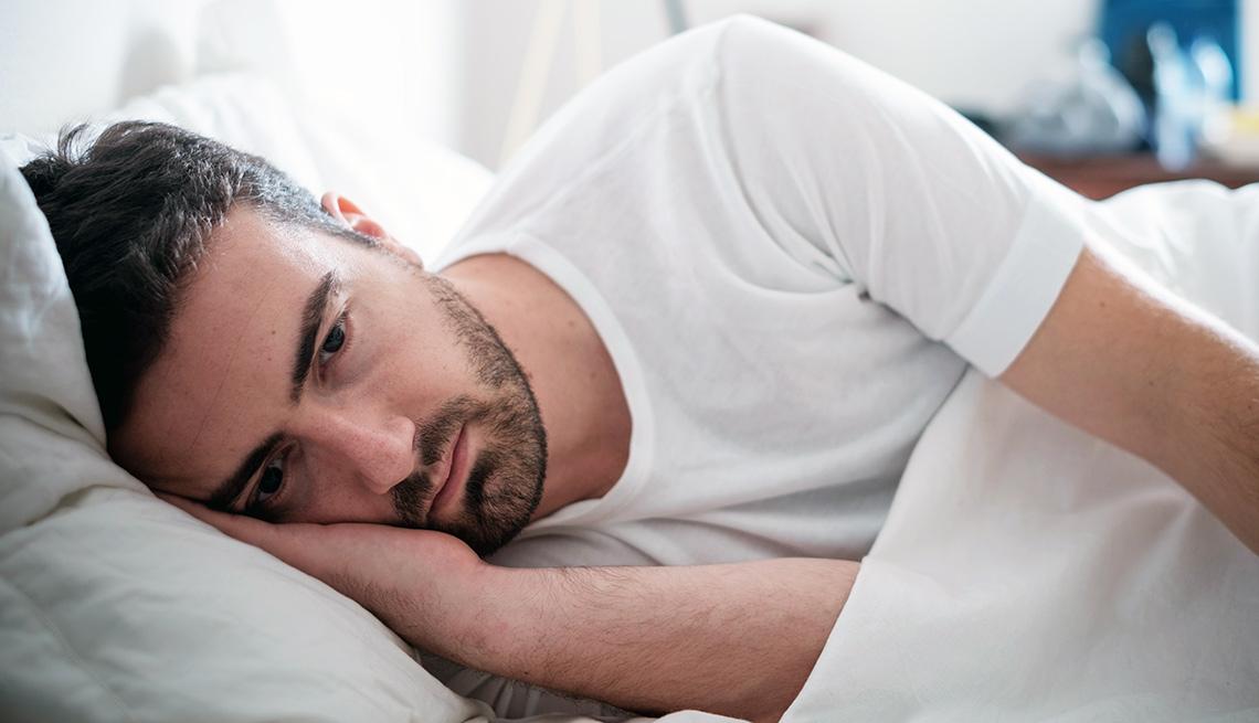 Hombre acostado sin poder dormir