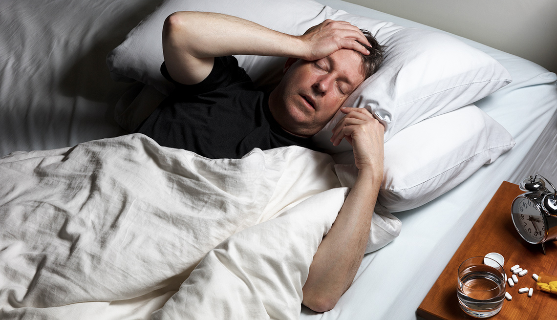 Man in bed experiencing pain with pills on table