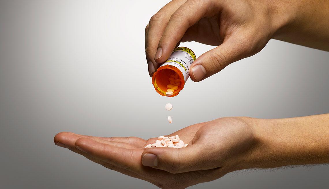 Persona vaciando las pastillas de un frasco en su mano