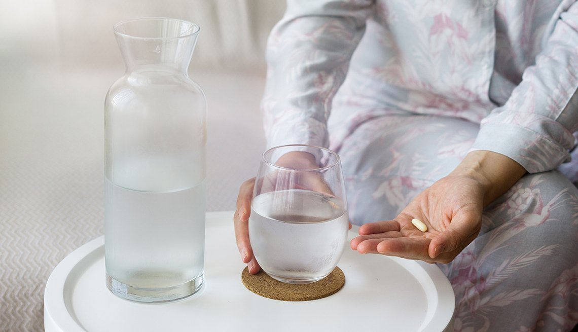 A woman taking a vitamin supplement with water