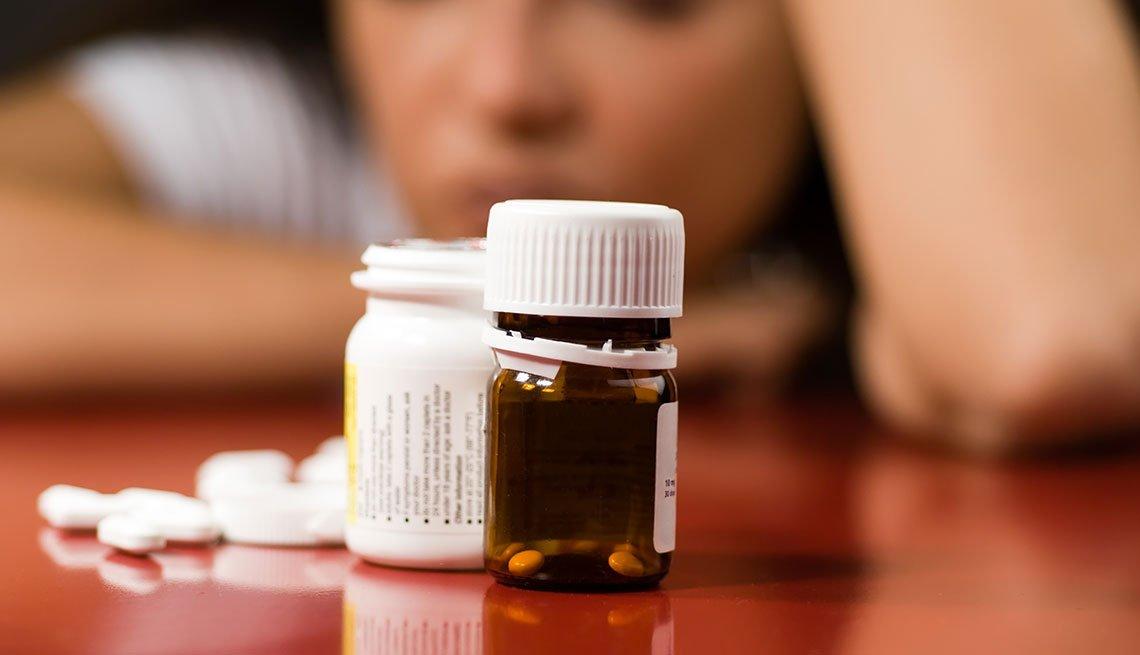 item 9 of Gallery image - Mujer deprimida mirando un frasco de pastillas