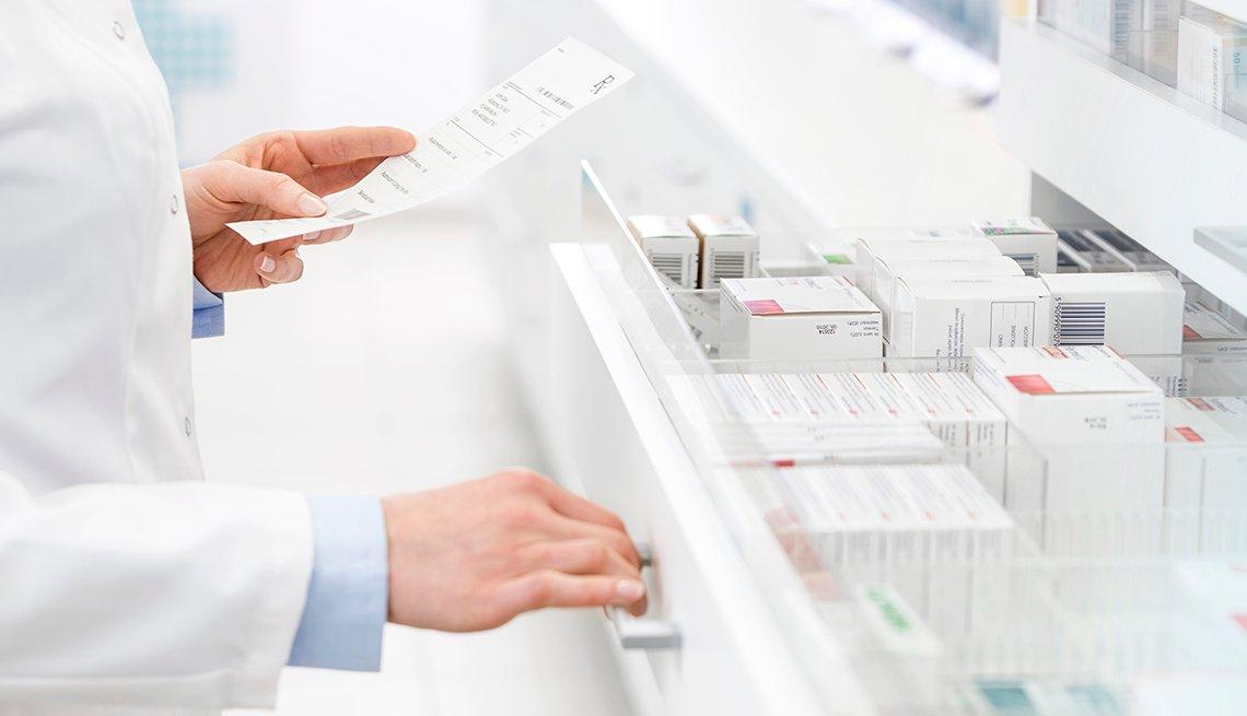 Pharmacist filling prescription in pharmacy. Opening a white drawer full of prescriptions.