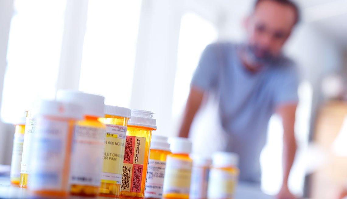 Hombre en el fondo y varios frascos de medicamentos en primer plano
