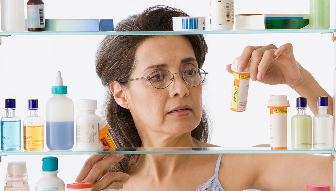 Woman taking medication in bathroom.