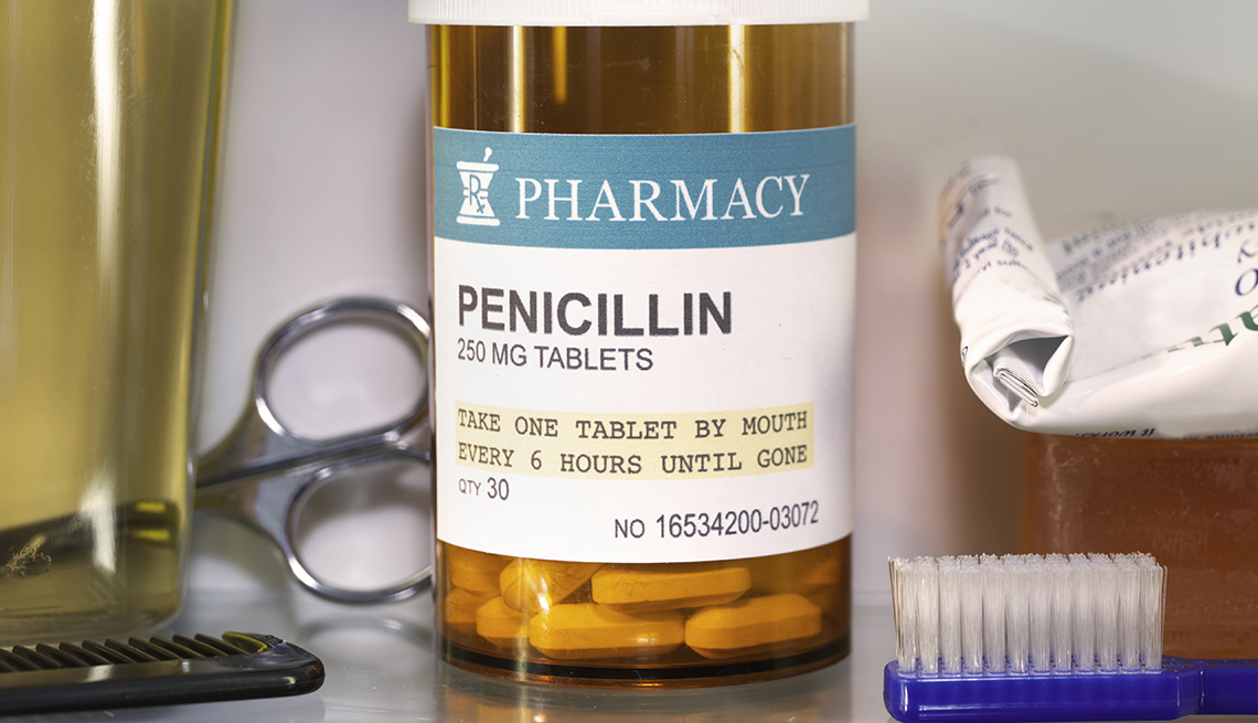 A pill bottle with a Penicillin label sitting in a medicine cabinet with a toothbrush and other toiletries.