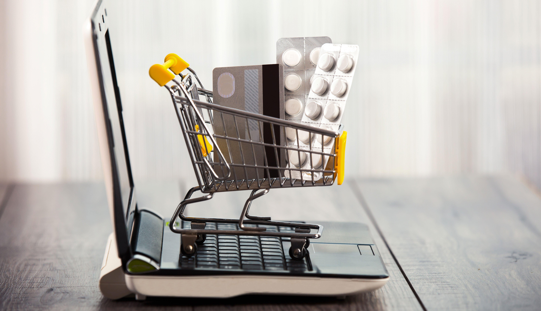 Carrito de compras, medicamentos, tarjeta de crédito y computadora