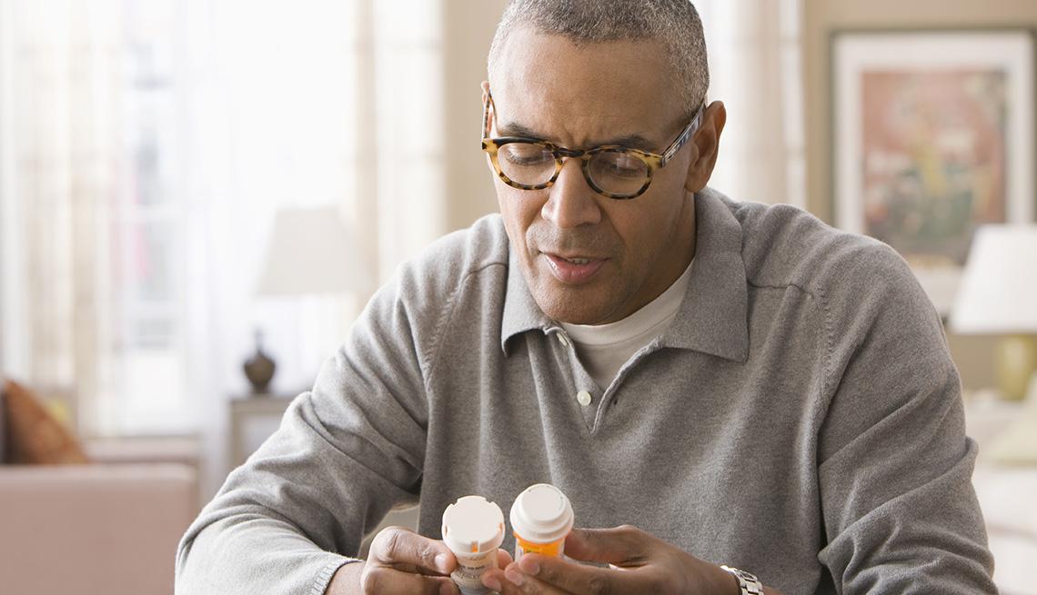 Hombre inspeccionando unos frascos de medicamentos