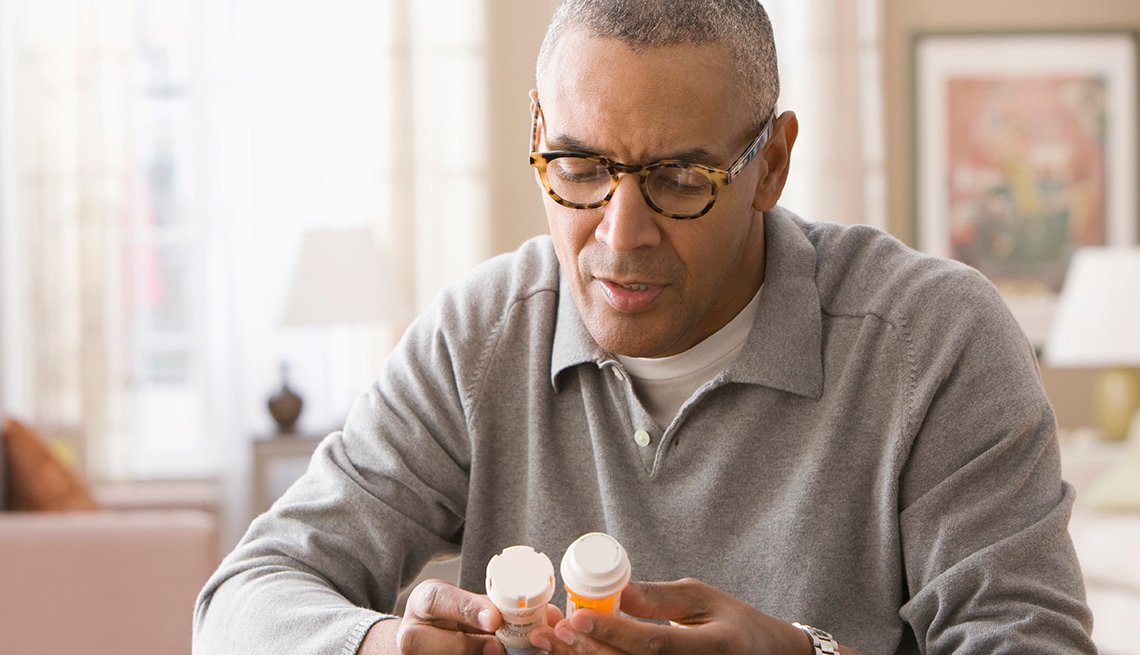 African American Man examining prescription bottles.