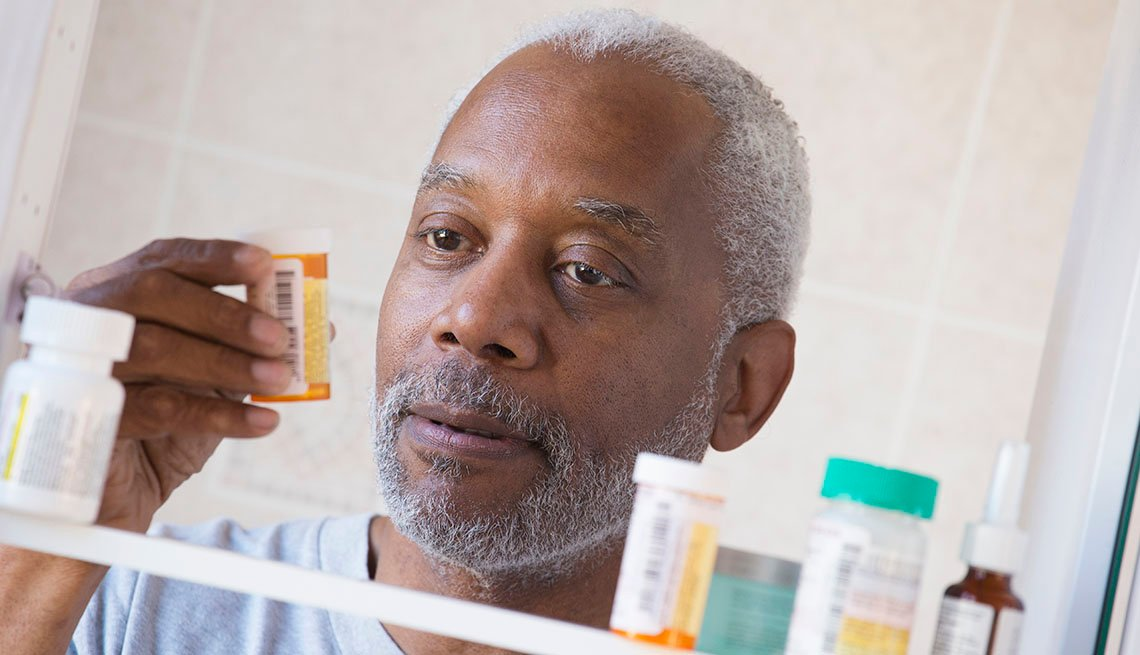 Man looks at prescription bottle at medicine cabinet