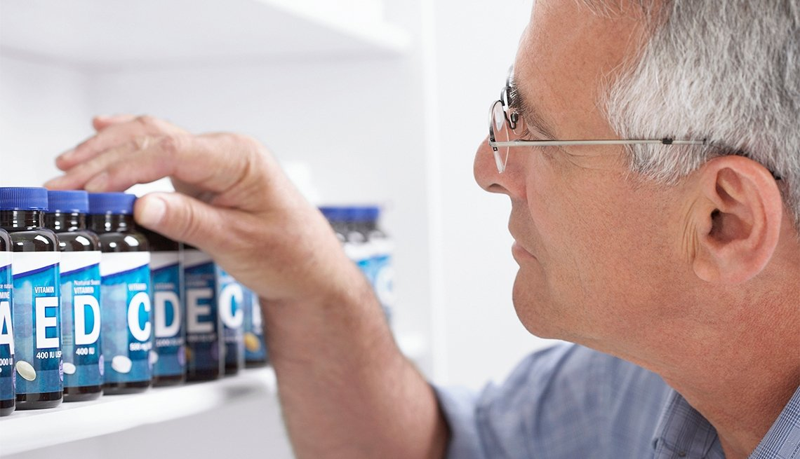 Man looks at supplement bottles