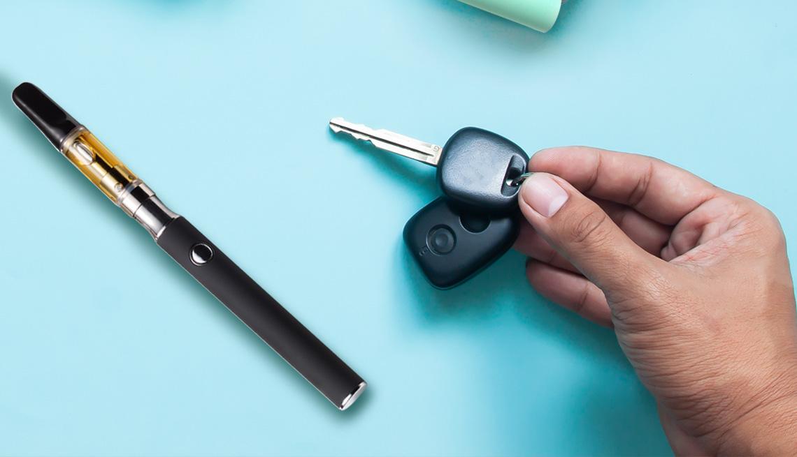 A man's hand reaching for car keys on a blue counter next to a marijuana vape pen