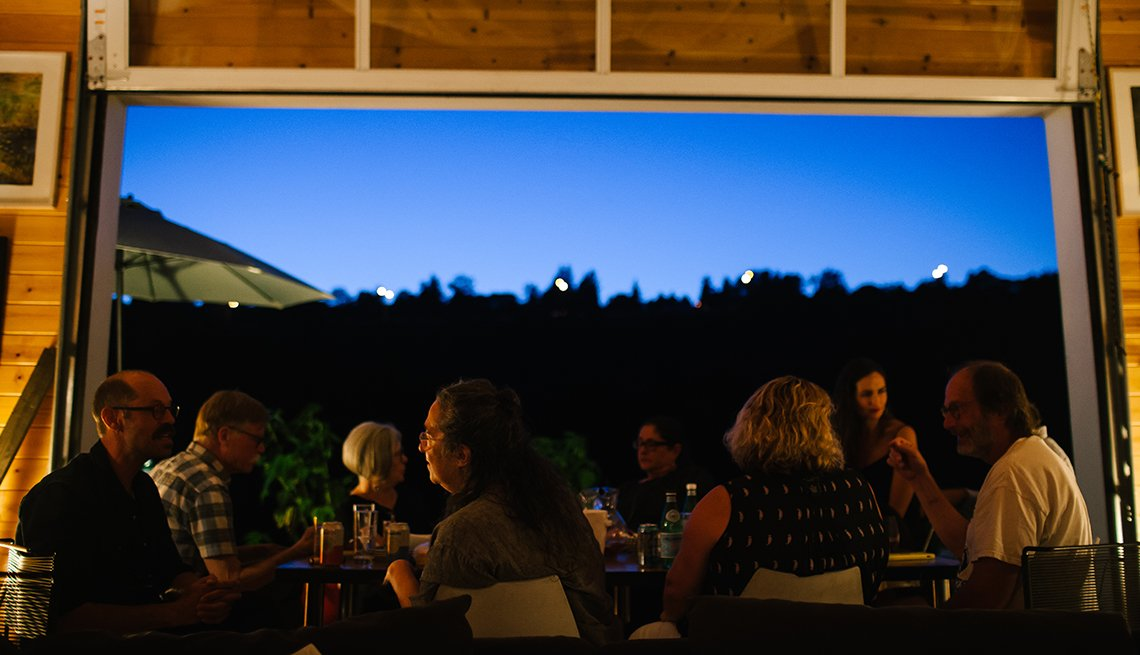 A group of eight people are seated at a table enjoying a meal next to an open garage door that shows a view of an evening sky