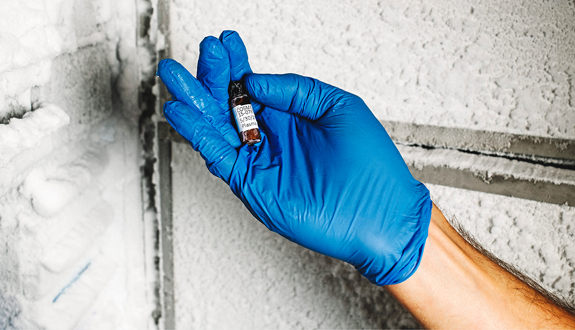 Una persona usa un guante médico azul y sosteniene una muestra de sangre