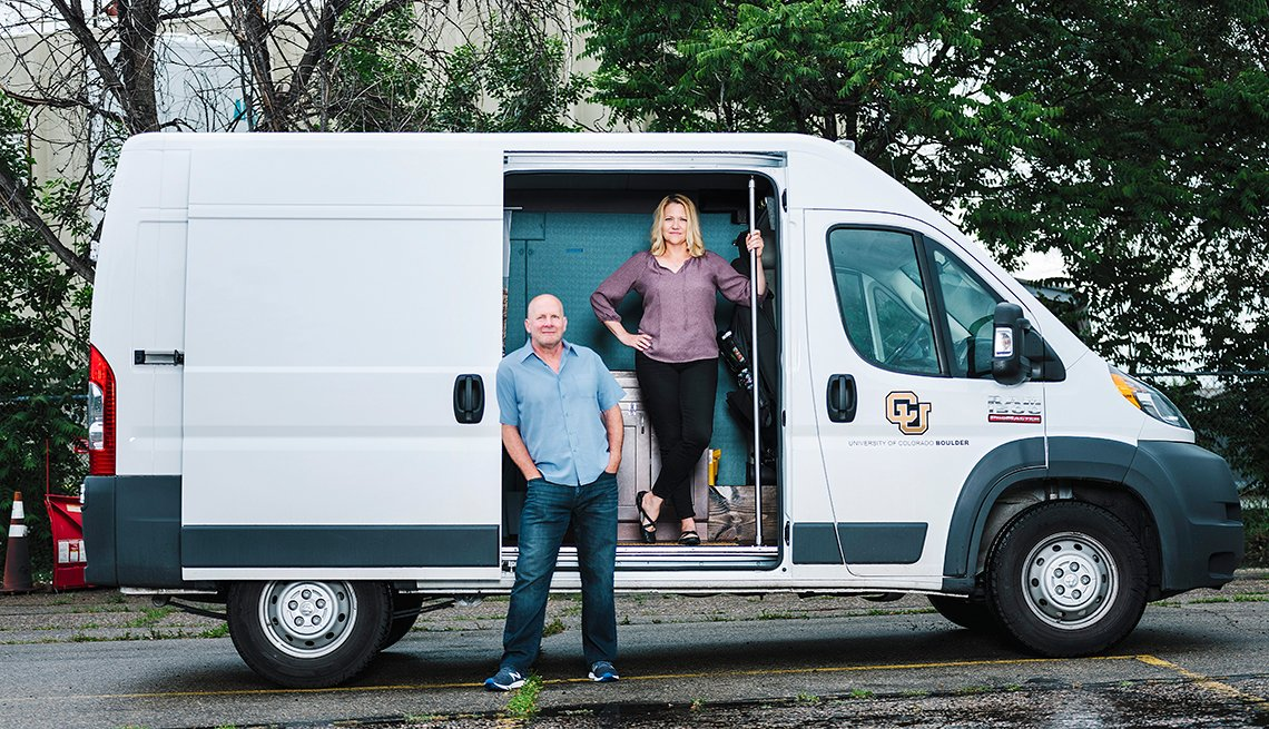 University of Colorado at Boulder professors Kent Hutchison and Angela Bryan stand in front of a white cargo van known as the CannaVan