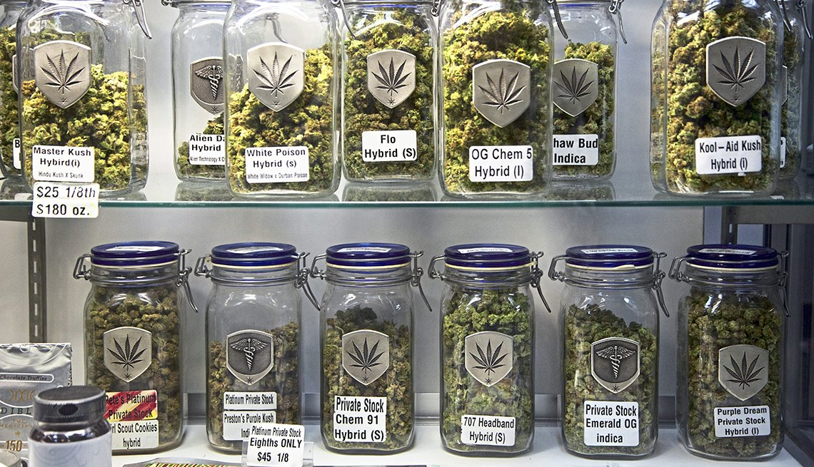 Two shelves holding over a dozen mason-jar-sized labeled glass jars containing marijuana buds of different strains