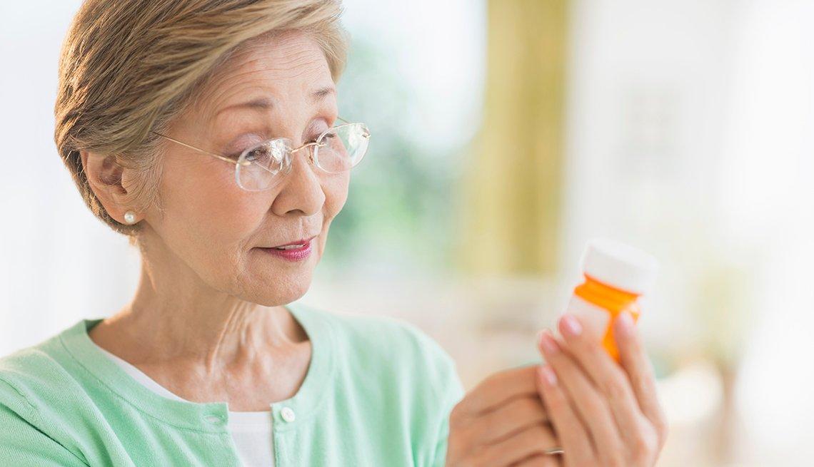 A woman reading the label on a prescription pill bottle