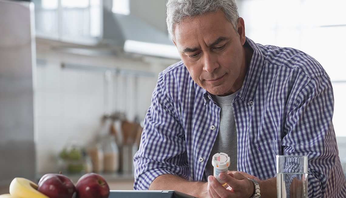 A man examining a prescription drug bottle in the kitchen