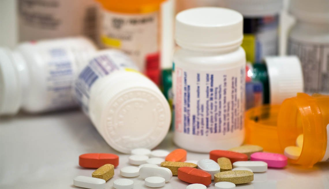 Prescription drugs on a table with many medication bottles