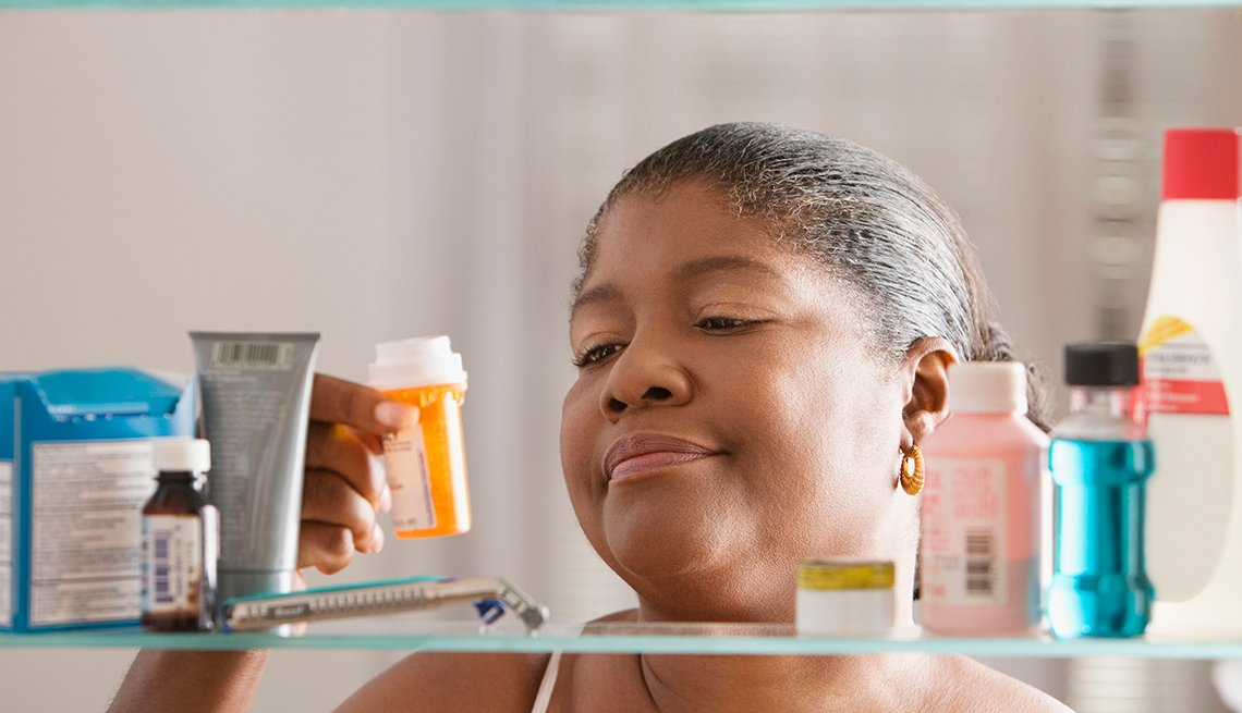 African American woman holding bottle of pills in front of medicine cabinet