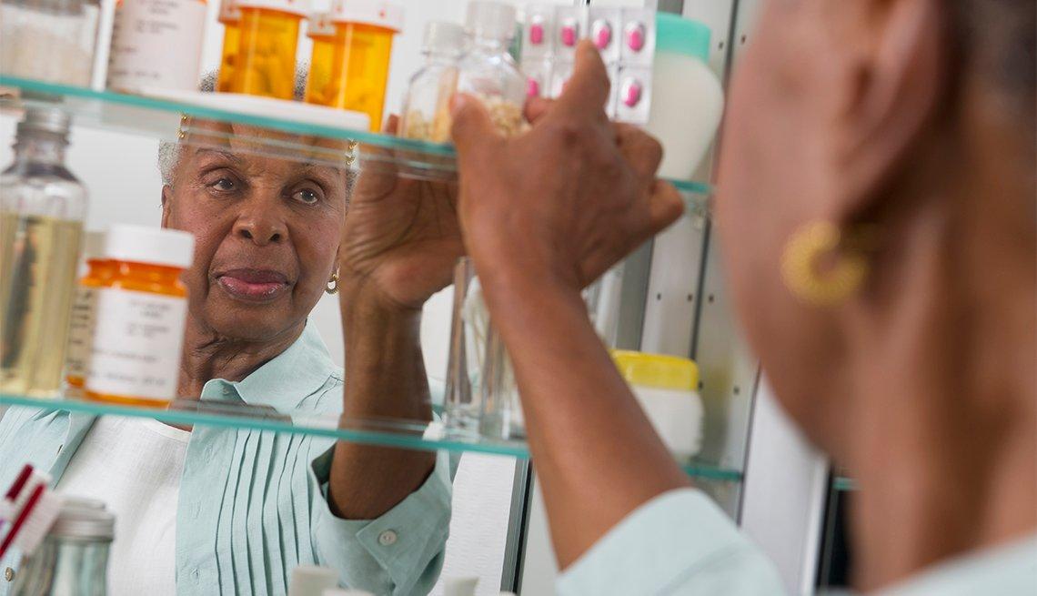 Una mujer revisa su botiquín de medicamentos