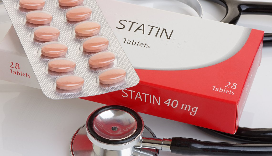 Statin pills on top of their box and a stethoscope nearby.