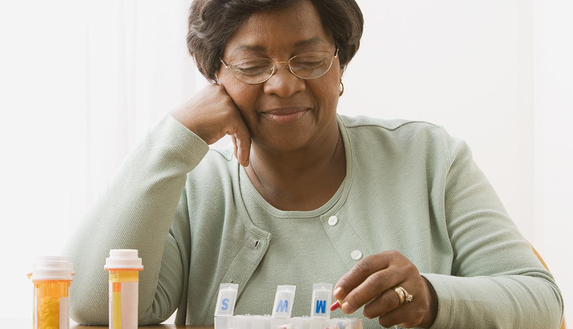 Mujer poniendo sus medicamentos recetados en un pastillero