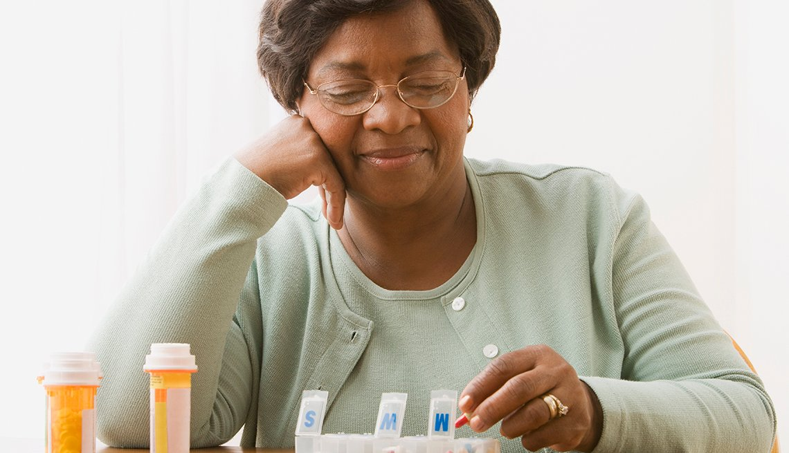 Woman putting her prescription medications in a pill box.
