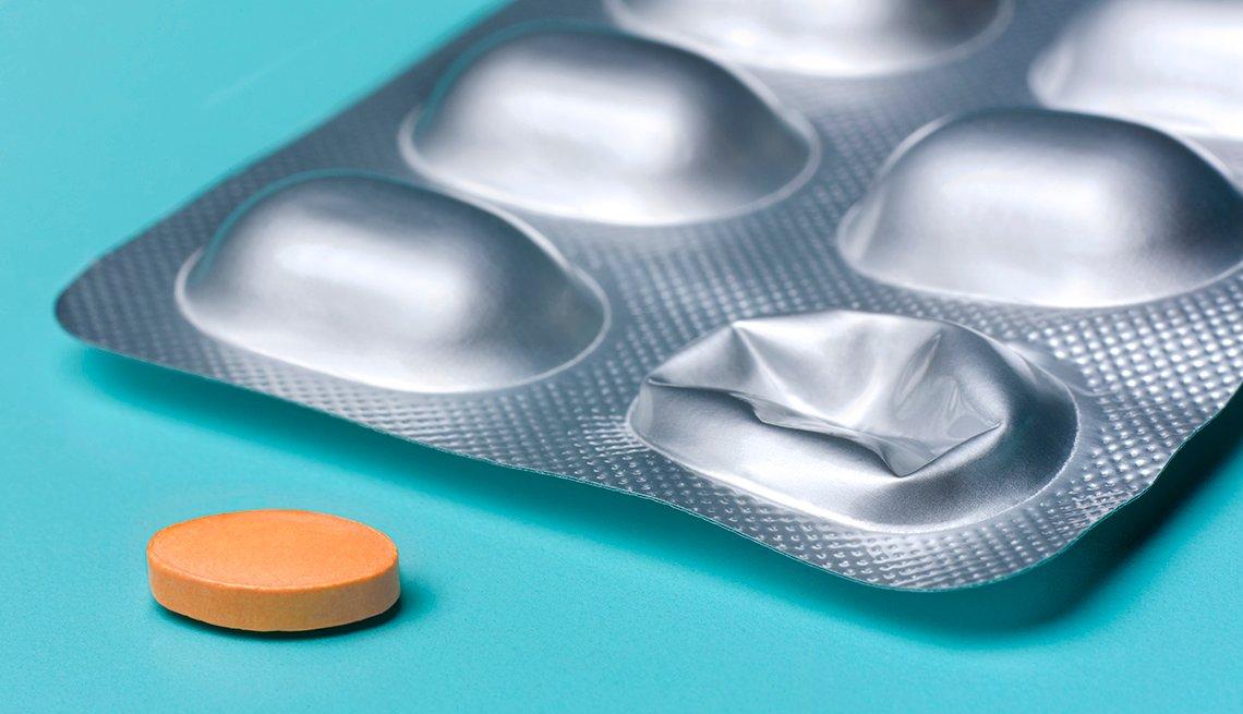 Una pastilla removida de su empaque, lista para tomar