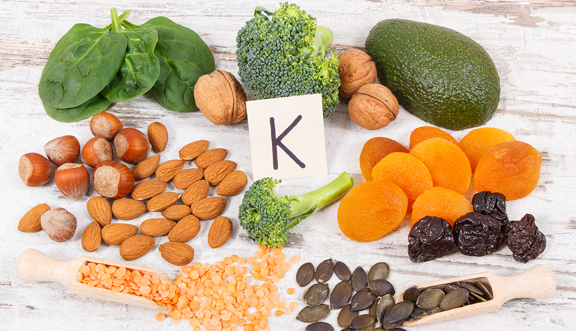 Fresh fruits and vegetables containing vitamin K, with the letter K