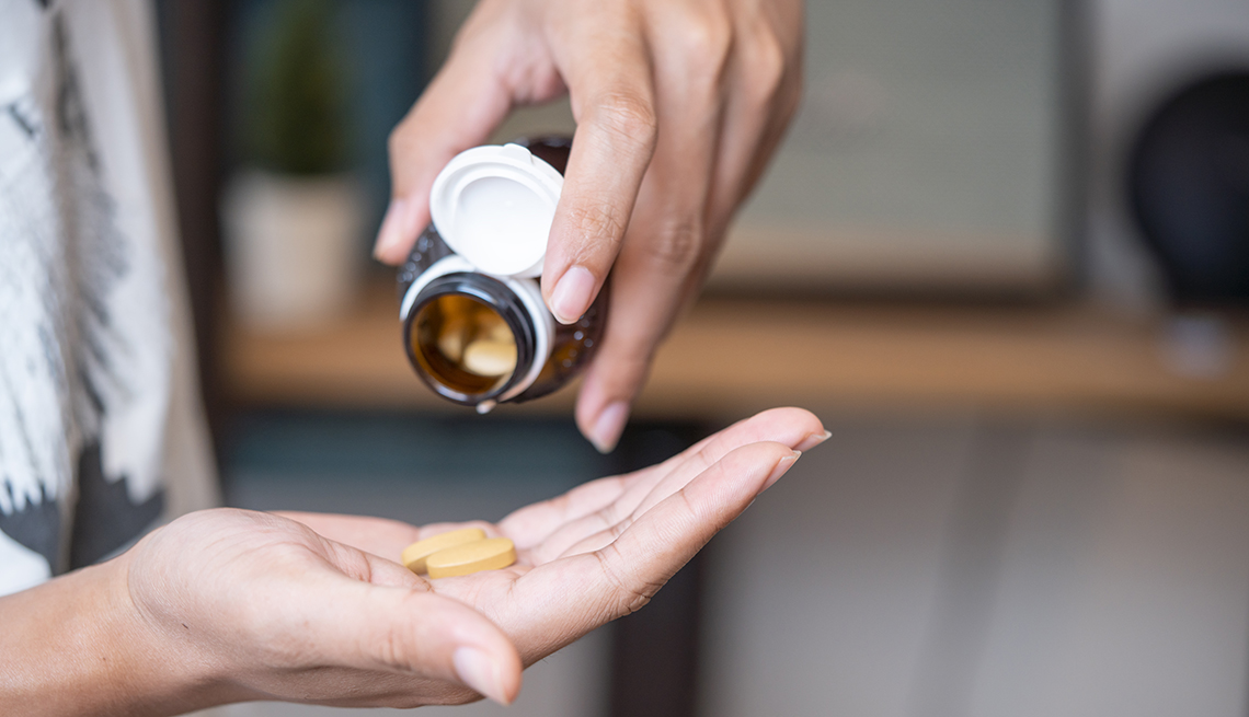 a person holding a pill bottle putting vitamins into their hand