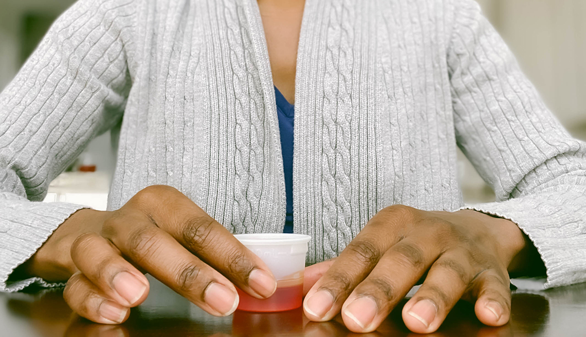close up of a woman's hands holding a small cup of cough syrup