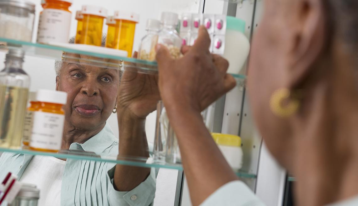 Una mujer busca un medicamento en su botiquín