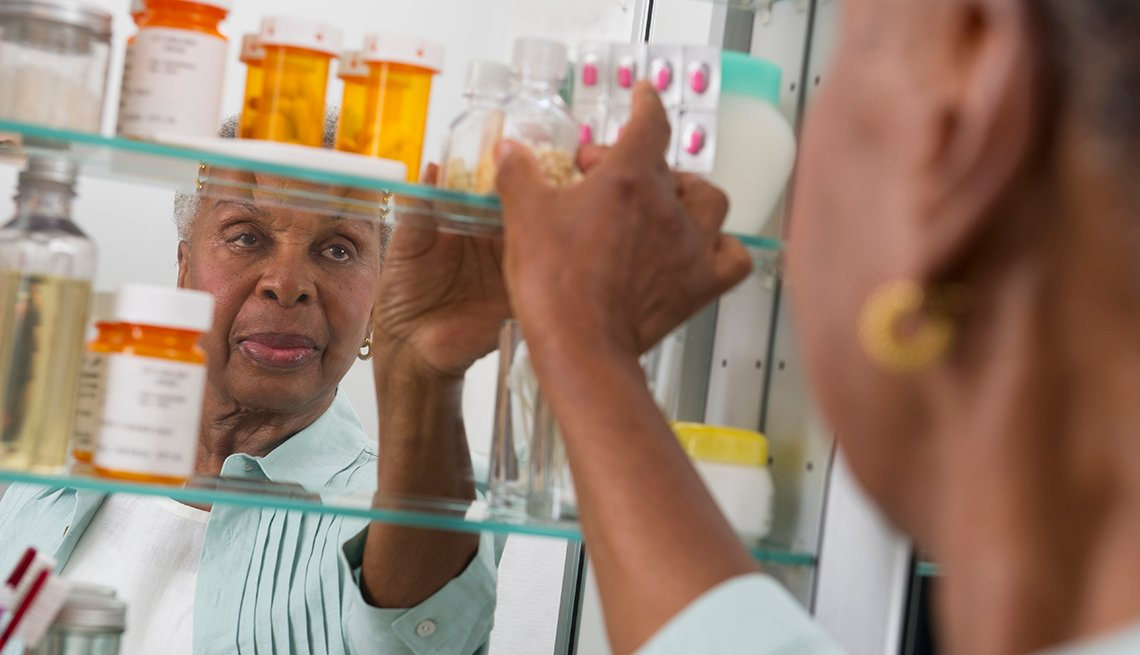 woman reaching into her medicine cabinet