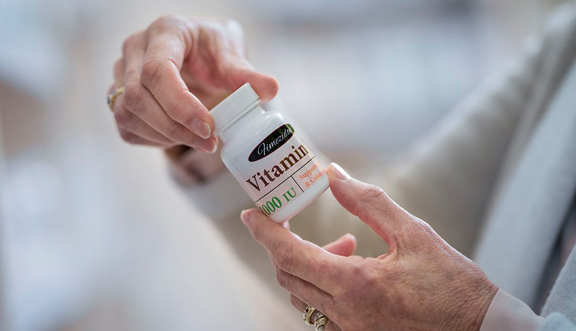 Close-up of woman's hand holding vitamin bottle in drugstore.