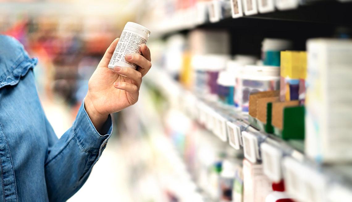 Cliente en una farmacia examina un frasco de pastillas que se vende sin receta