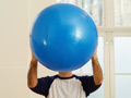 Mature man holding exercise ball in front of face