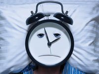 man with alarm clock head having trouble sleeping
