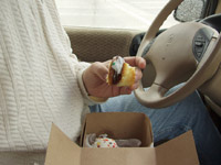 Man eating cupcake inside car