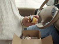 Man eating cupcake inside car