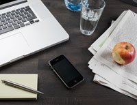 An office desk with laptop, water, apple and smart phone