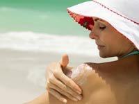 Consejos del Dr. Oz para cuidar la piel este verano - Mujer en la playa aplicándose protector solar.
