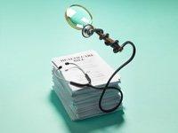 Papeles de la reforma de Salud con estetoscopio y una lupa