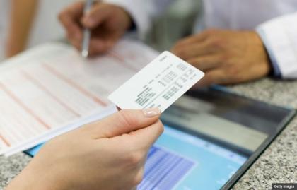 Mujer entrega una tarjeta de seguro de salud a un profesional de la medicina - Informacion sobre el mercado de seguros (Obamacare)